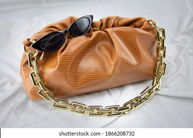 Women handbag with black sunglasses on a white background. Leather bag on a gathered fabric. Side view fashion concept of fancy fashionable glasses and Luxury Genuine Full Grain Leather handbag