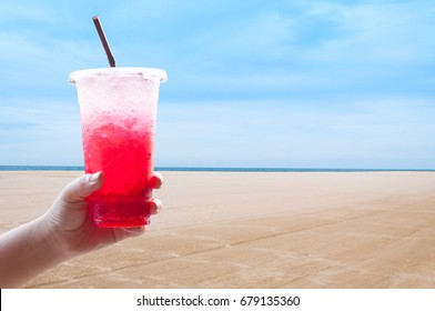 Women handle holding ice water italian soda red in plastic cup,Red, sweet  cool drink in the summer at the beach, during the holidays