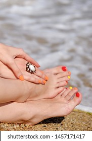 Women hands and feet with a bright manicure and pedicure on the background of a sea surf. Vacation holidays