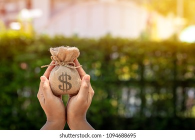Women hands hold a money bag in the public park for loans to planned investment in the future concept.