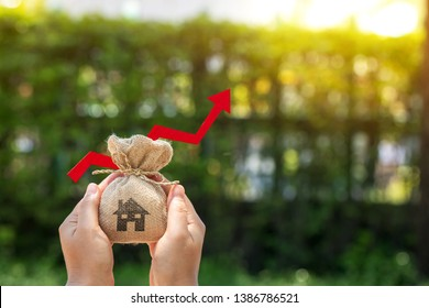 Women hands hold a money bag with a house symbol and red arrow graph with growing value in the public park, Loan and business investment for real estate concept.
