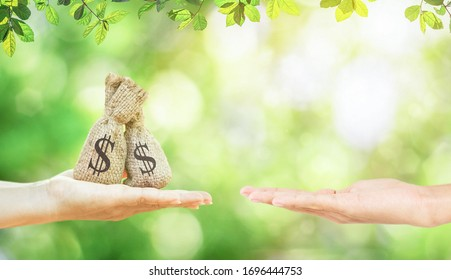 A women hands hold a money bags in the public park and men for loans to planning savings money of coins buy a home concept for property mortgage. - Shutterstock ID 1696444753