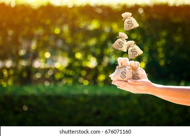 Women hands hold a money bags and dropping on the top in the public park for loans to planned investment in the future concept.