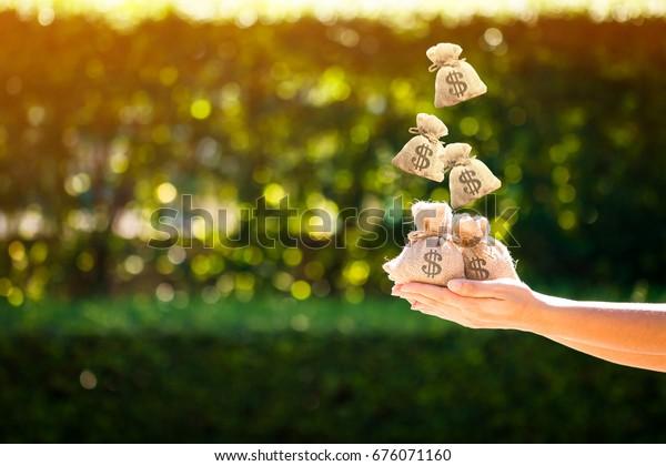 Kobiety ręce trzymać torby z pieniędzmi i spada na górę w parku publicznym dla kredytów planowanych inwestycji w przyszłej koncepcji.