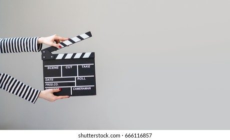 Women hands holding clapper board for making video cinema in studio.Movie production clapper board or slate film concept.