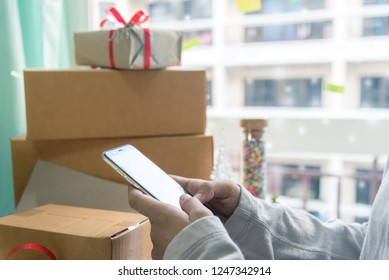 Women Hands holding Credit Card and Using SmartPhone by the Burning Fireplace and Festive Presents - Close Up. Man with phone key-green screen by cozy fireside.