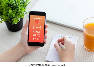 Women hands holding phone with app for health card monitoring and writing in a notebook