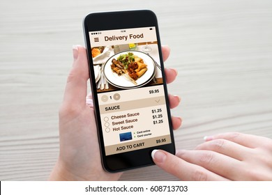 Women hands holding phone with app delivery food on screen over table