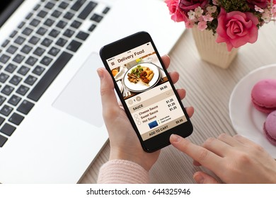 Women hands holding phone with app delivery food screen near laptop in cafe