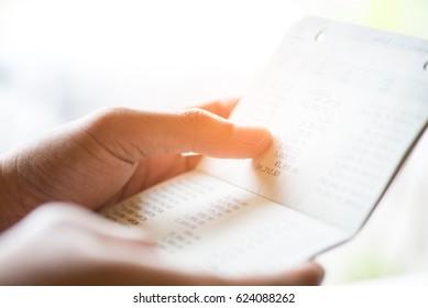 Women hands holding saving account passbook, book bank  laptop background