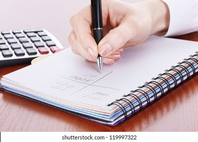 women hands with pencil, notebook and Calculator on wooden table