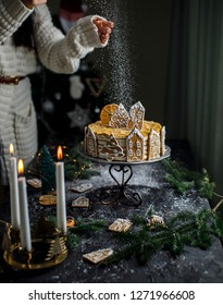 Women hands are pouring suger powder, snowing on the Christmas New year cake, homemade gingerbread cookies