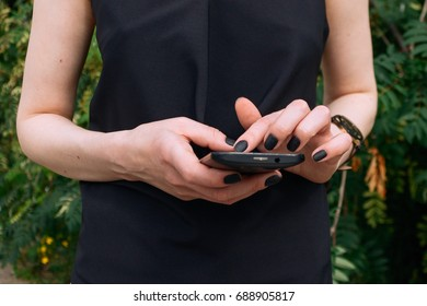 A women hands with smartphone. Black nails and black mobile phone.