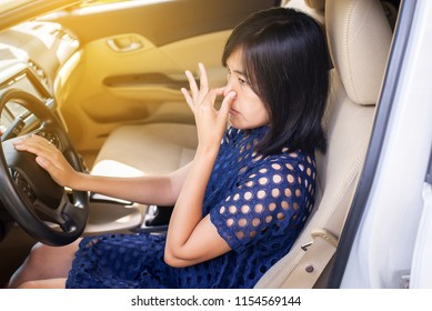 Women hands squeeze her nose with of bad smell in a car