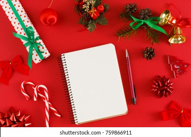 Women hands writing shopping list for xmas. Christmas staff on red background with copy space on notebook. Point of view, crop