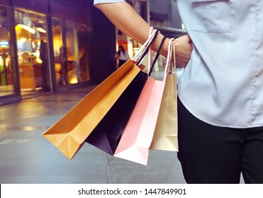 Women hanging shopping bags in her hand and acting hands on waist.