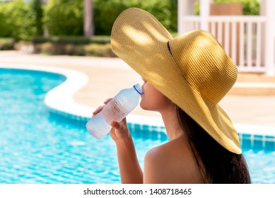 Women have long hair, wearing a big hat Drinking cold water from plastic bottles Near the pool, to summer concept.