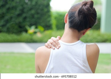 Women have neck pain, shoulder pain, at the park health concept.