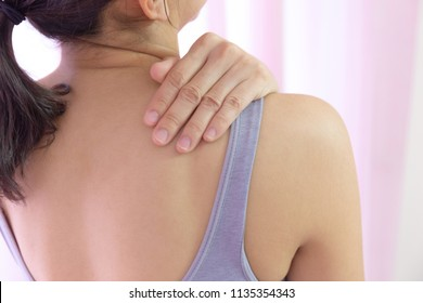 Women have shoulder pain and holding hand on muscle. young girl with sports exercise pain at indoor hospital. trapezius muscle scapular bone swelling and inflammation for medical doctor body concept.