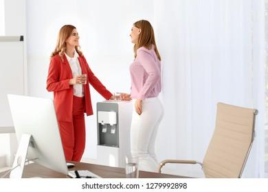 Women having break near water cooler at workplace
