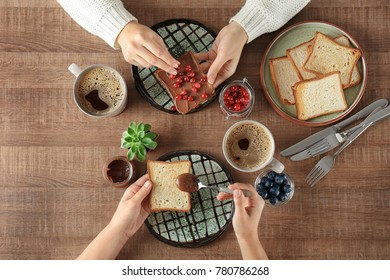 Women having breakfast with toasts at table, top view