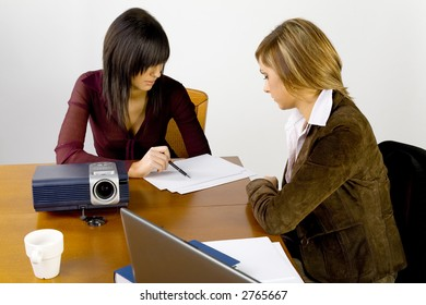 Women having conversation at conference's table. There's multimedia projector and laptop on it.