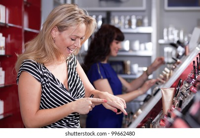 Women having fun while buying and testing cosmetics in a beauty store