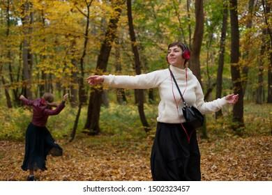 Women in headphones dance in the park in autumn
