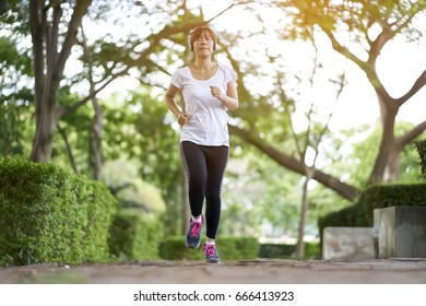 Women with headphones jogging and relaxing stroll in the park happy.