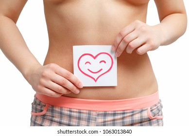 Women Health. Closeup Of Healthy Female With Beautiful Fit Slim Body Holding White Card With Happy Smiley Face heart shaped In Hands. Stomach Health And Good Digestion Concepts. High Resolution