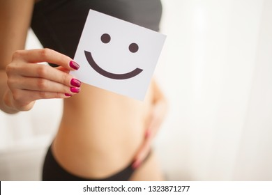 Women Health. Closeup Of Healthy Female With Beautiful Fit Slim Body In White Panties Holding White Card With Happy Face In Hands. Stomach Health And Good Digestion Concepts. High Resolution