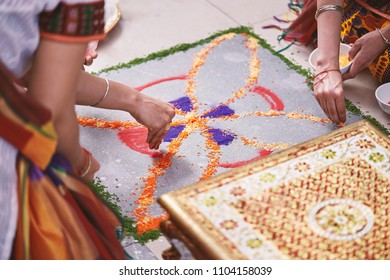 Women helps coloring tradition colorful rice art or sand art (Rangoli) on the floor with paper pattern using dry rice and dry flour with colored from natural pigments like sindoor, haldi (turmeric)