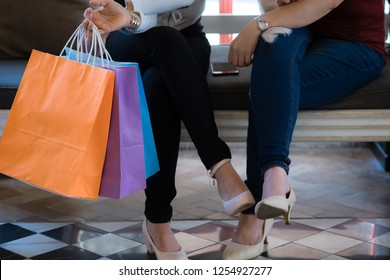 Women with high heels and shopping bags - Two girls sitting on sofa and talking after buying presents