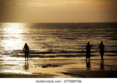 Women in hijab standing at the beach in sunset in Malaysia