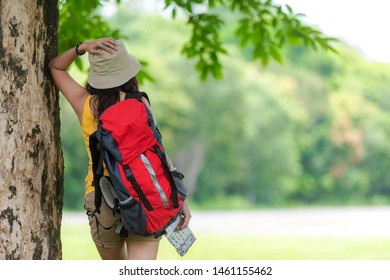 Women hiker or traveler with backpack adventure holding map to find directions and walking relax in the jungle forest outdoor for education nature on vacation. Travel and Lifestyle Concept