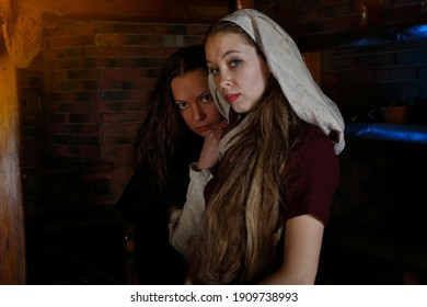 Women in historical costumes. Portraits of two maids in a tavern. A scene from medieval life. Historical reconstruction of a restaurant lunch. Girls in vintage dresses and  old headscarf. Renaissance - Shutterstock ID 1909738993