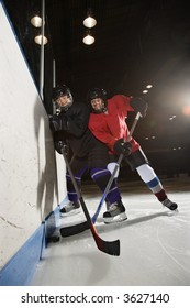 Women hockey players fighting for puck making contact.