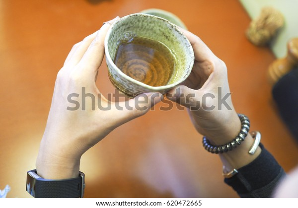 Women hold a cup of Chinese hot tea in the restaurant