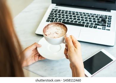 Women hold a cup of coffee  while looking at laptop in cafe.