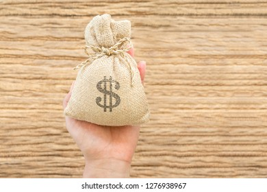 Women hold a money bag on the vintage wood background, a loan or saving money for future investment concept.