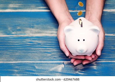 Women hold a pig bank and a drop gold coins on the vintage blue background, a saving money for future investment concept.