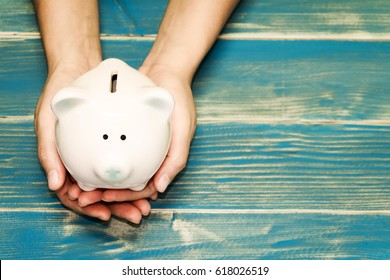 Women hold a pig bank on the vintage blue background, a saving money for future investment concept.
