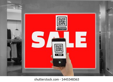 Women hold smartphone in hand,scan store QR code to e- coupon check price receive promotion and discount,cashless society concept ,application for shopping,fast communication and modern technology 4.0