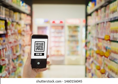Women hold smartphones in hand,scanning store QR code to check prices,receive promotions and discount in supermarket,cashless society concept,application for shopping,and modern technology 4.0