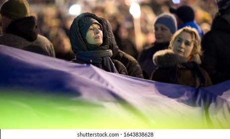 women hold a very large Ukrainian national flag. Ukrainian nationalists torchlight procession (torch march) 111th anniversary of the birth of Stepan Bandera. January 1, 2020 Kyiv, Ukraine