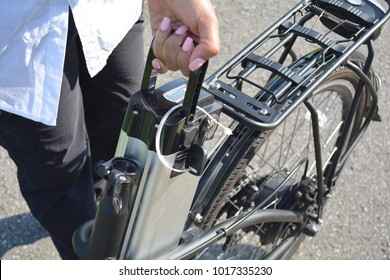 Women holding battery pack of electric bicycle near her e bike. Female taking out e bike battery. Visible motor and gear on the back wheel.  Ecology concept. Charging batteries. Renewable energy.