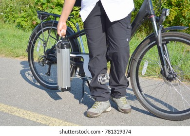 Women holding battery pack of electric bicycle near her e bike. On the background is e bike back wheel with electro motor and gear.  Ecology concept.