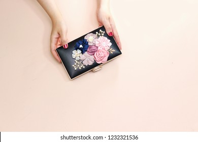 women holding beautiful floral black clutch, wedding bag isolated on pink background