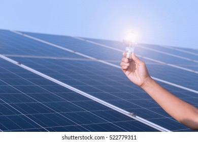 women holding the bulb on solar panels , Solar Energy ,The concepts of Clean Energy.