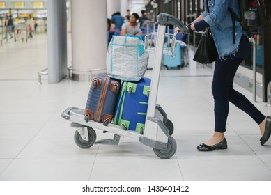 women holding cart of suitcase or baggage in the international airport.